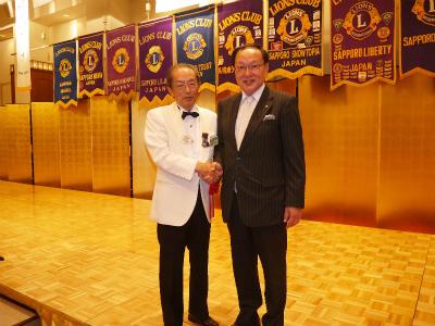地区ガバナーと当クラブ会長の握手